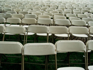 rows of empty white folding chairs