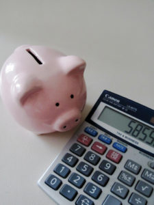 piggybank next to a calculator-are you counting pennies for your book