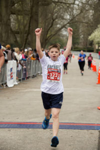 boy crossing race finish line with his arms in the air to celebrate