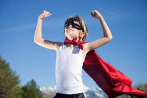 boy wearing goggles and cape like a superhero costume