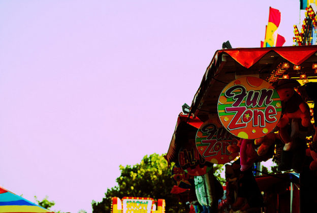 colorful picture of boardwalk storefronts with sign saying fun zone