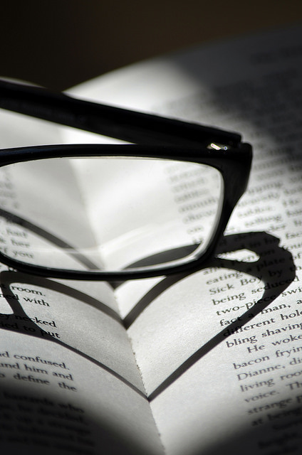 the shadow of reading glasses on an open book makes a heart shape